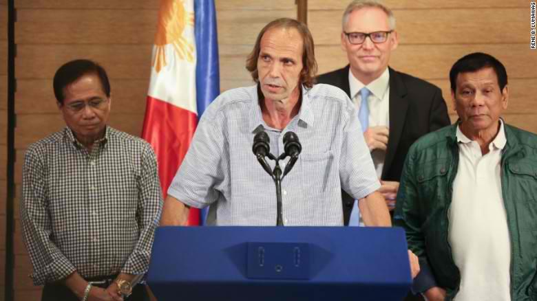 Propuštěný Nor na tiskové konferenci. Vpravo filipínský president Duterte.